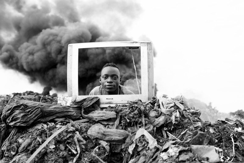 A young boy is playing behind a discarded TV frame at the Hulene dump in Maputo. Many electronic items are sent to the dump every day, and the people who live and work on the site recycle them for reuse and resale on the black market. They also have to navigate the huge number of items which will not see reuse. There is limited regulatory oversight on e-waste processing in Mozambique, and e-waste is causing serious health and pollution problems in the area.